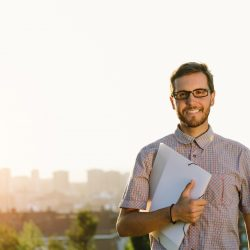 Successful professional person outside holding certification pack